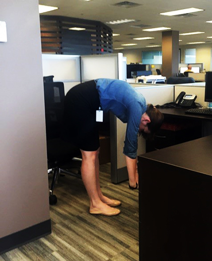 A woman stretches at her desk