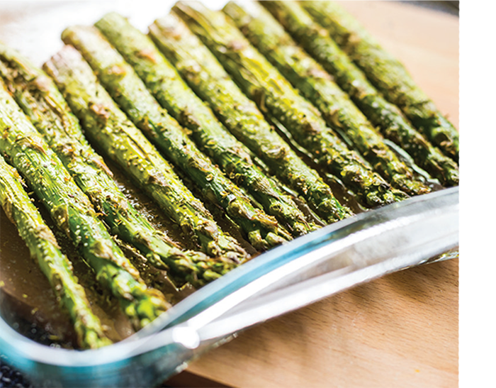 A dish holds grilled asparagus