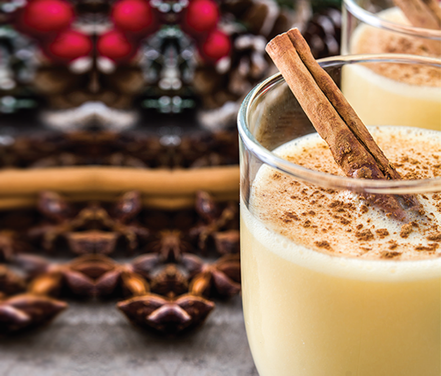 A glass of healthy eggnog with cinnamon sticks